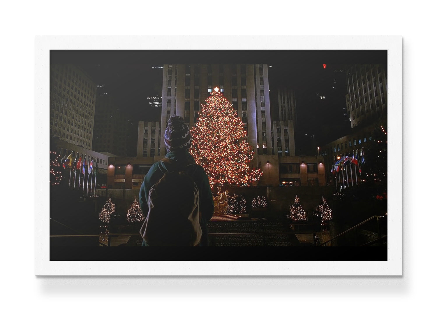 Photo de Kevin dans Maman, j'ai encore raté l'avion, à New-York, devant le sapin de Noël du Rockefeller Center.